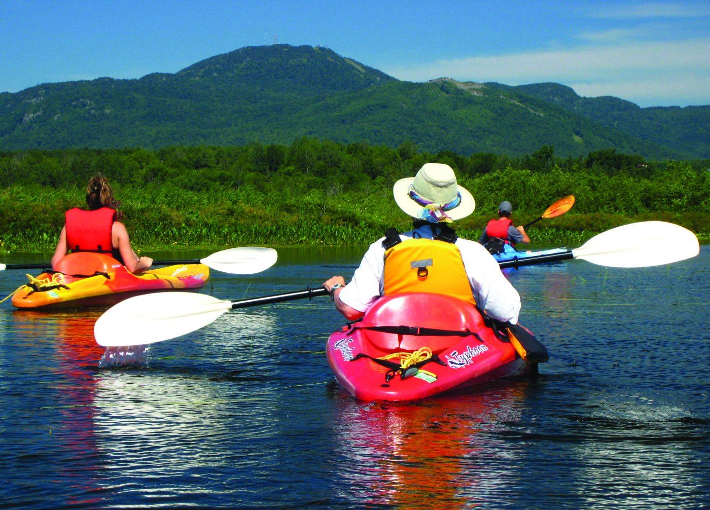 Trois personnes de dos chacun sur des kayaks colorés. Au loin, de la verdure et le Mont Orford
