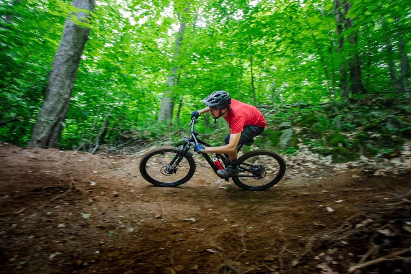 Homme avec un t-shirt rouge et un casque noir qui effectue un virage dans un sentir de terre dans la forêt sur son vélo de montagne