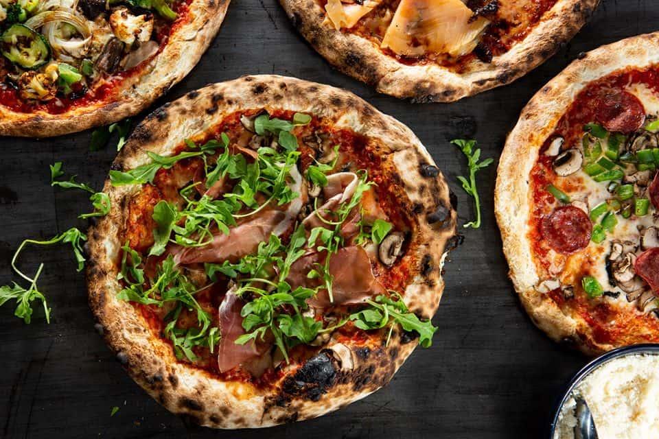 Quatre pizzas de style napolitain vue d'en haut sur un fond d'ardoise. Dans le coin inférieur droit, un pot de parmesan avec une cuillère à l'intérieur.