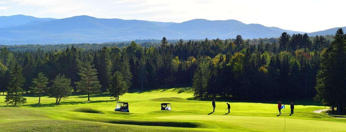 Vue panoramique d'un terrain de golf avec la pelouse très verte. Quelques golfeurs jouent. Au loin, la forêt et les montagnes.