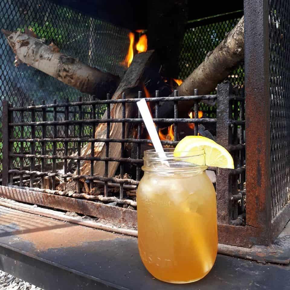 Thé glacé avec paille et tranche de citron sur le bord d'un feu de foyer extérieur
