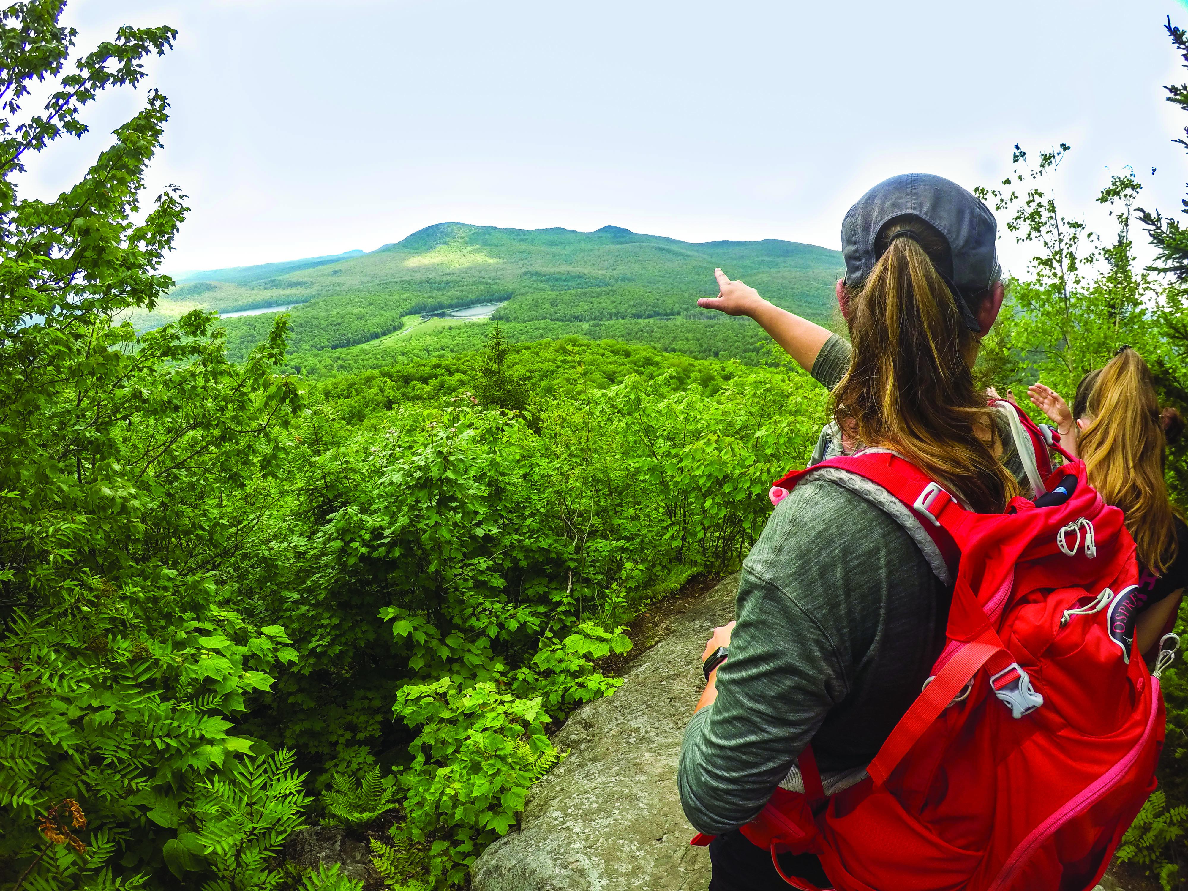 Femme de dos avec un sac à dos rouge qui pointe vers l'horizon au sommet d'une montagne en été.