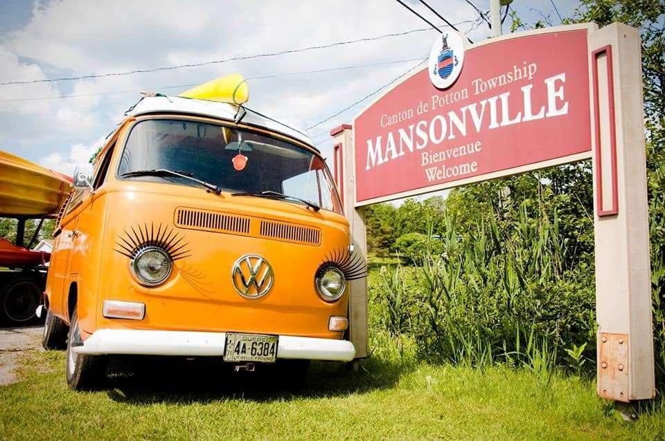 Wesfalia jaune avec un kayak sur le toit devant le panneau de la ville de Mansonville