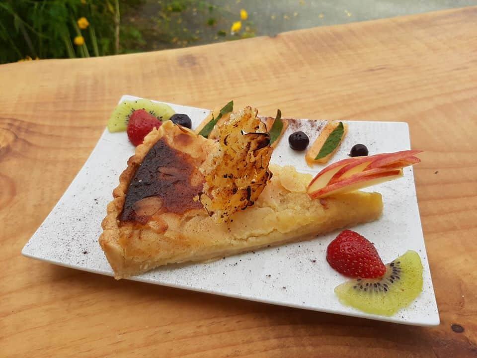 Tranche de tarte avec fruits frais sur une assiette rectangle blanche