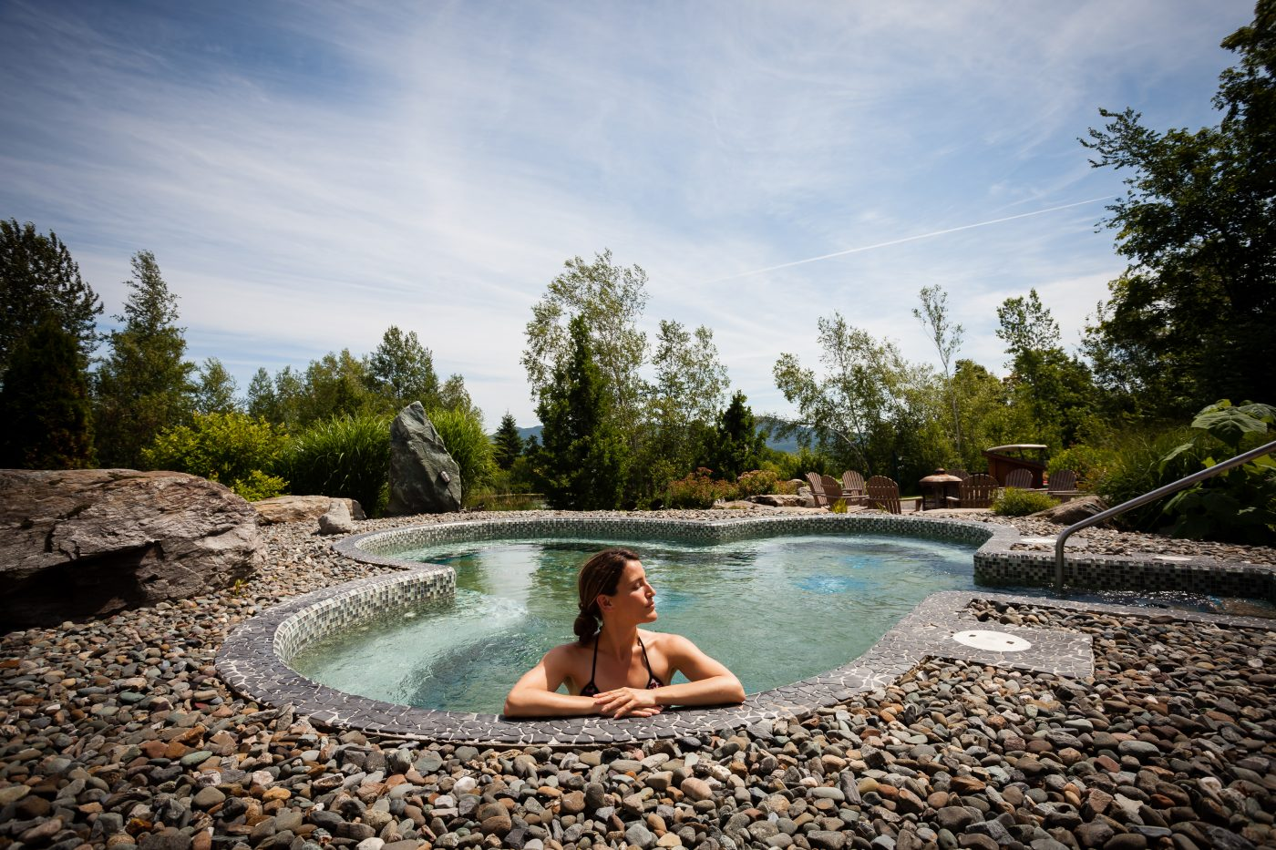 Femme dans un bain à remous en forme de trèfle accotée sur le rebord de roche. Au loin, on aperçoit la forêt et le ciel parsemé de légers nuages.