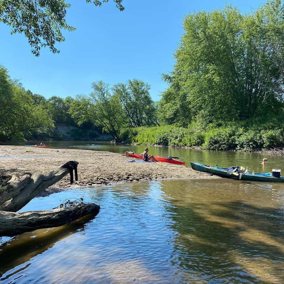 Bord de rivière dans la forêt. Sur la plage de roches des kayaks sont stationnée. Un kayakiste prend une pause sur la plage.