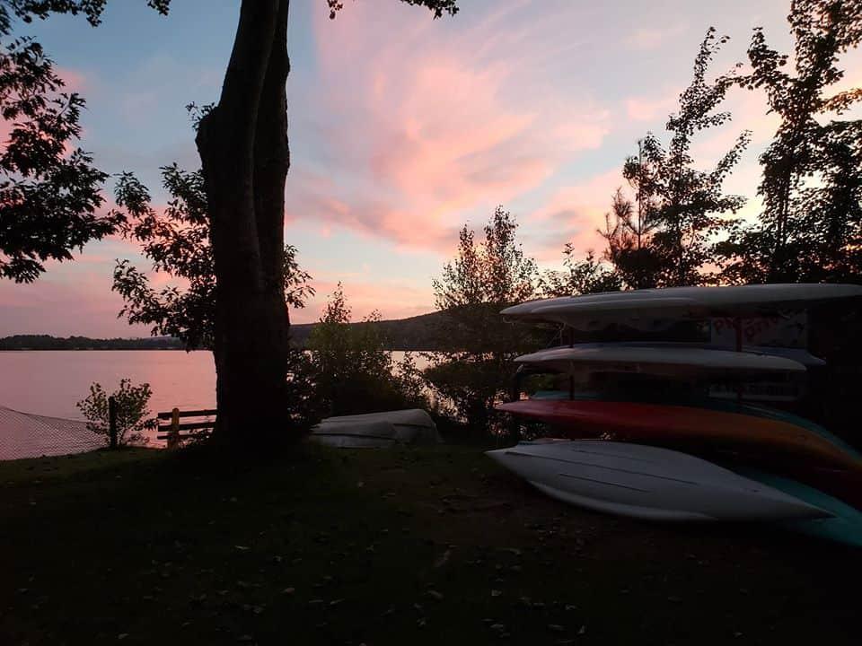 Rack plein de kayak sur le bord d'un lac au coucher de soleil.