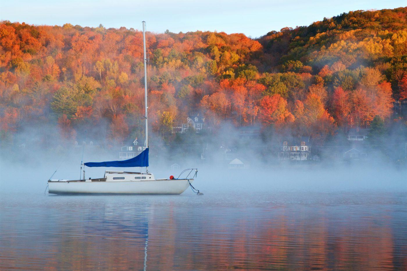 Voilier au milieu du lac Massawippi avec les arbres orangés aux couleurs d'automne