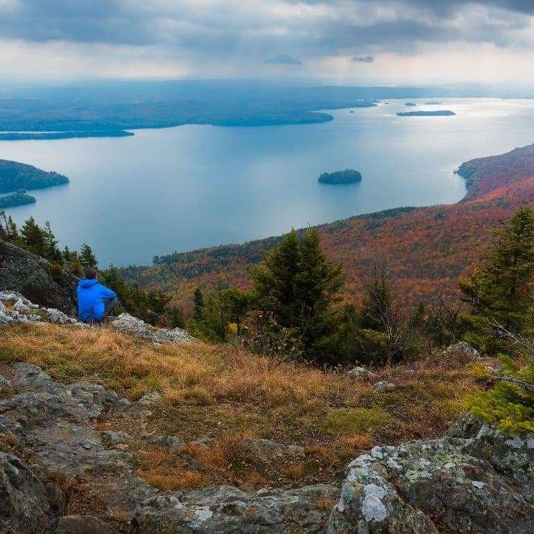 Homme au sommet du mont Owl's Head qui admire la vue sur le lac Memphrémagog